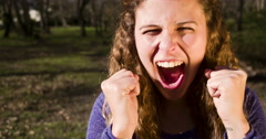 Excited young beauty yelling and cheering with clenched fists in air Stock Footage