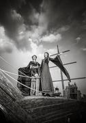 Two elegant woman in extravagant antique luxury clothes on boat - stock photo