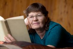 Cute senior woman absorbed in reading - stock photo