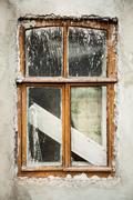 Dilapidated white stucco wall with wooden window dirty in paint - stock photo
