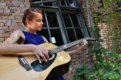 teenage girl playing acoustic guitar in the street - stock photo