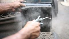 Cleaning the air filter of the engine via a flow of compressed air - stock footage