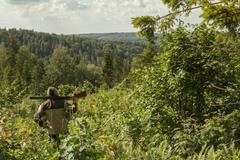 Mari man with gun overlooking rural landscape Kuvituskuvat