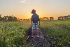 Mari boy standing in tire tracks in rural field Stock Photos