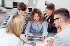 Five Office People Looking at the Tablet Together - stock photo