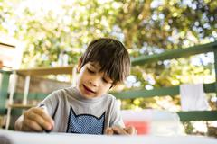 Mixed race boy coloring on porch Stock Photos