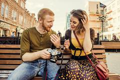 Stock Photo of Caucasian couple checking photos on digital camera