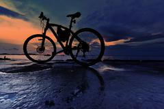 Stock Photo of Silhouette of bicycle parking beside sea with sunset sky