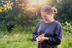 Caucasian woman holding chick in garden Stock Photos