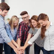 Happy Office People Putting Hands on One Another - stock photo