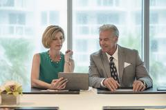 Caucasian business people using digital tablet in meeting Stock Photos