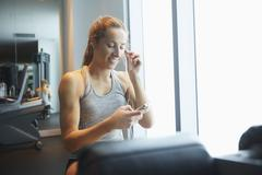 Woman listening to mp3 player in gym Kuvituskuvat