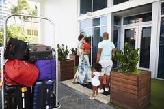 Black family walking into hotel lobby Stock Photos