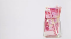 Stock Video Footage of 100-Chinese Yuan Bills In Glass Jar - Camera Turning Around