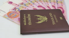 100-Chinese yuan bills with Thai passport on the table Stock Footage