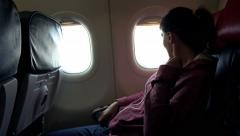 Young woman looking out of the window during plane flight 4K - stock footage