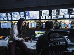 Security guards watching monitors in control room Stock Photos