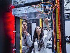 Technicians examining computer in server room Stock Photos