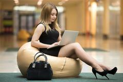 Stock Photo of Young woman with laptop in public wifi area