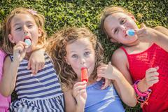 Stock Photo of Girls eating flavored ice in grass