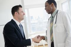 Businessman and doctor shaking hands in office Stock Photos