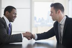 Businessmen shaking hands in office meeting Stock Photos
