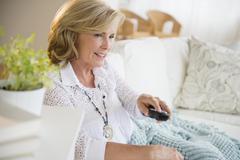 Caucasian woman watching television on sofa Kuvituskuvat