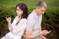 Couple absorbed in phone communication Stock Photos