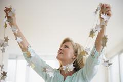 Caucasian woman decorating with garland in living room Stock Photos