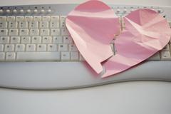 Close up of broken heart on computer keyboard Stock Photos