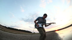 Guitarist musician man playing solo on electric guitar by river at sunset sky Stock Footage