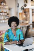 African American business owner using laptop in store Stock Photos