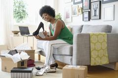 African American woman opening packages of shoes on sofa Kuvituskuvat