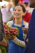 Clerk holding produce at farmers market - stock photo