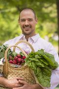 Caucasian man carrying basket of fresh produce Stock Photos