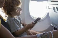 Caucasian mother and baby son using cell phone on airplane Kuvituskuvat