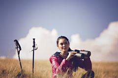 Hiker looking in binoculars enjoying spectacular view on mountain top - stock photo