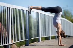 Street yoga: Downward facing Tree Pose variation Stock Photos