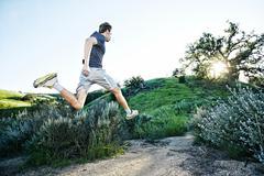 Caucasian athlete running on rural trail Stock Photos