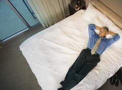 Caucasian businessman laying on hotel bed Stock Photos