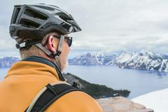 Stock Photo of Caucasian cyclist admiring view of Crater Lake, Oregon, United States