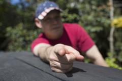 Mixed race man pointing finger on picnic table Stock Photos