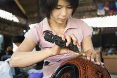 Asian artisan carving traditional design in workshop Stock Photos