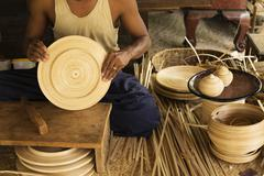 Asian artisan weaving traditional baskets in workshop Stock Photos