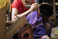 Stock Photo of Asian artisans carving traditional design in workshop