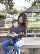 Stock Photo of Hispanic mother wearing son in carrier in park