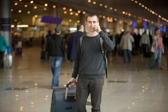 Young traveler in airport making call - stock photo