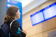 Girl looking at airport flight information board - stock photo
