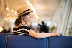 Young female traveler sitting in waiting lounge Stock Photos