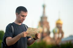 Stock Photo of Young traveler sightseeing with map